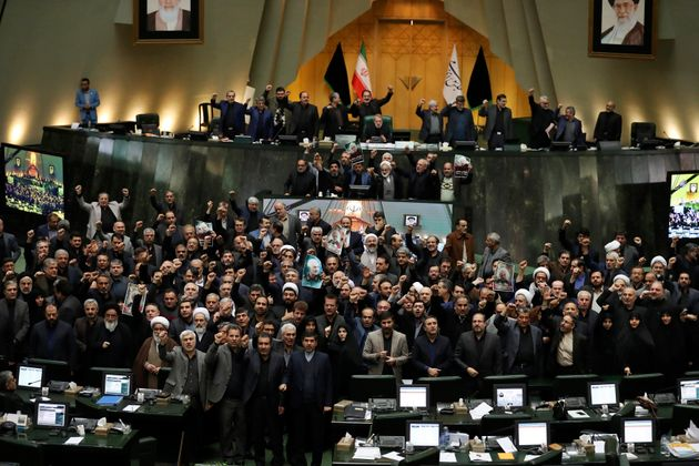 Iranian lawmakers chant slogans as some of them hold posters of Gen. Qassem Soleimani, who was killed...