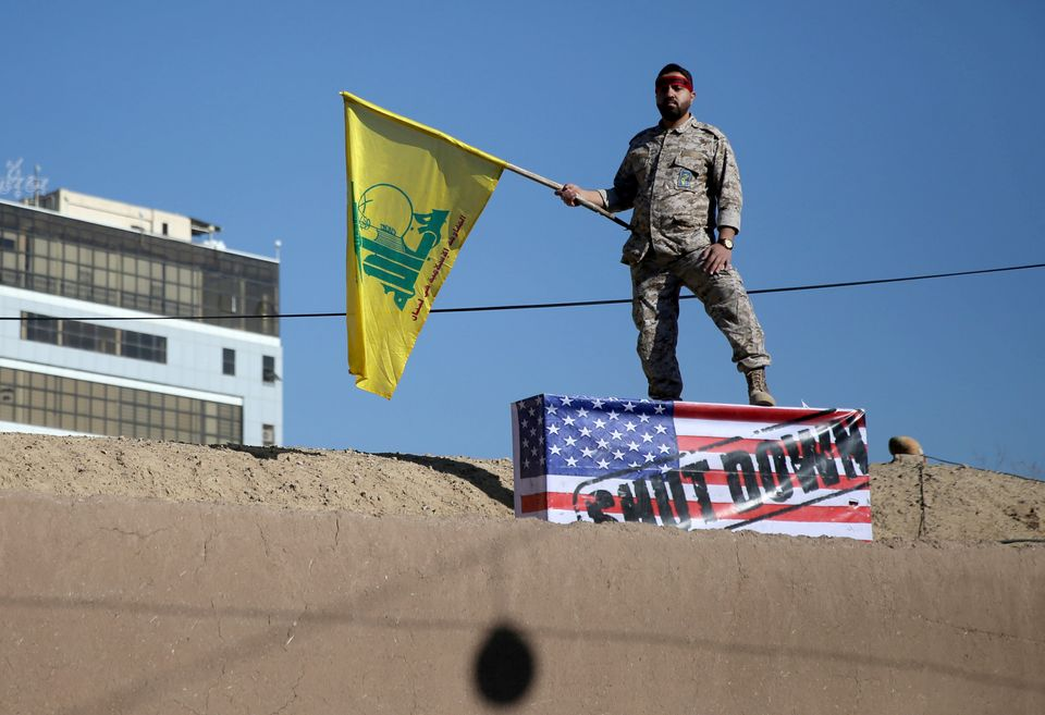 An Iranian guard holds a Hezbollah flag during a funeral procession and burial for Iranian Major-General...
