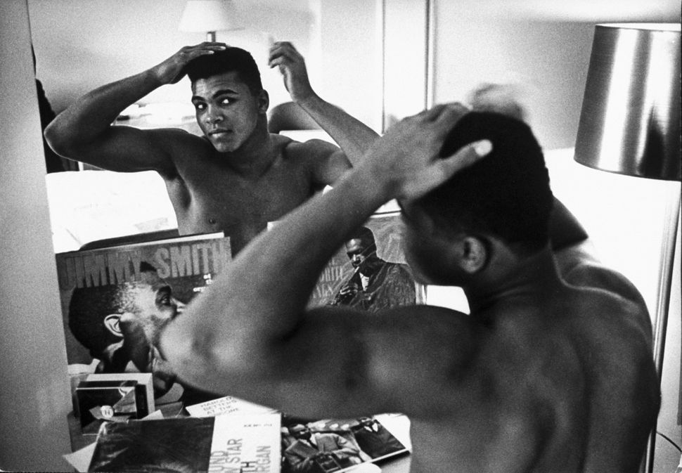 The boxing heavyweight contender then known as Cassius Clay combs his hair in the mirror in a Pittsburgh hotel room on Jan. 2