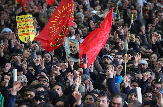 Iranian mourners carry a picture of Iran's supreme leader Ayatollah Ali Khamenei Qassem Soleimani during...
