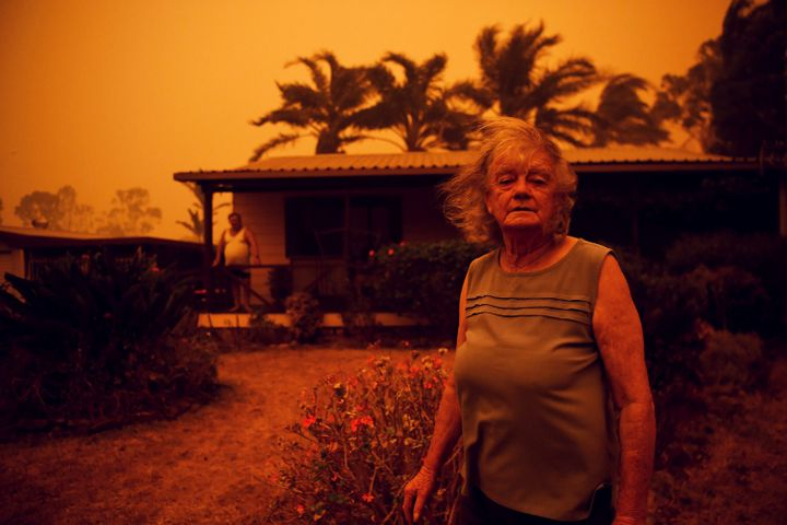 Nancy Allen and Brian Allen stand outside the house as high winds push smoke and ash from the Currowan Fire toward Nowra, New