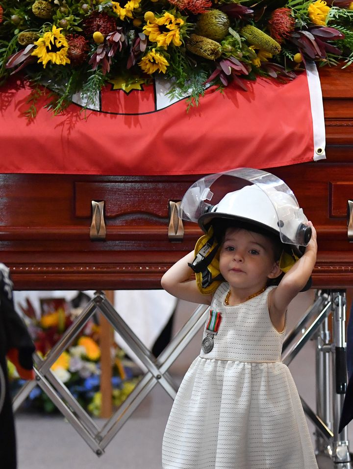 Charlotte O'Dwyer, the young daughter of Rural Fire Service volunteer Andrew O'Dwyer, stands in front of her father's casket wearing his helmet after being presented with his service medal during his funeral on Tuesday. O'Dwyer was one of three firefighters killed in recent fires.