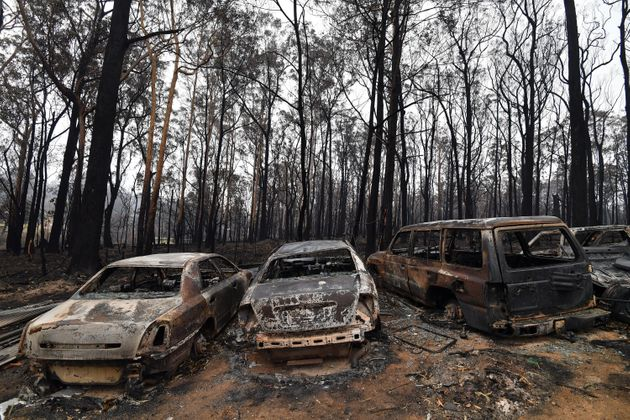 Charred vehicles that were gutted by bushfires in Mogo Village, New South Wales, are seen on