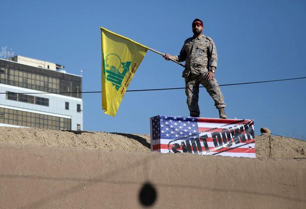 Guarda iraniano com a bandeira do Hezbollah (um dos grupos, também chamados de proxies, financiados...