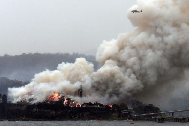 TOPSHOT - A military helicopter flies above a burning woodchip mill in Eden, in Australia's New South...