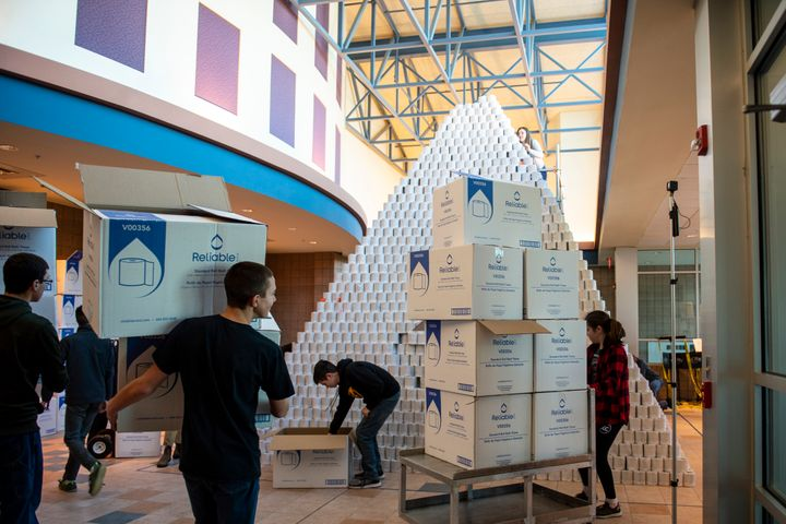 People involved in the Bullock Creek High School Robotics team prepare to take down the world's largest toilet paper pyramid