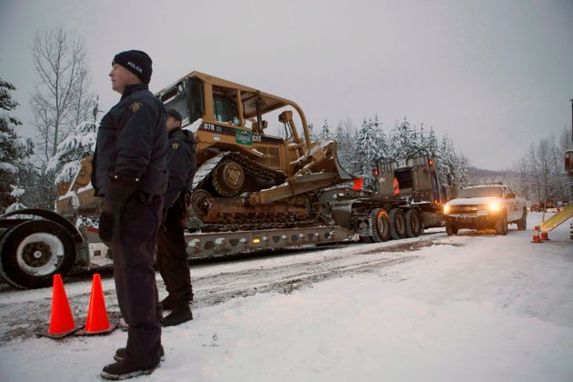 RCMP officers look on as contractors pass through their roadblock as supporters of the Unist'ot'en camp...