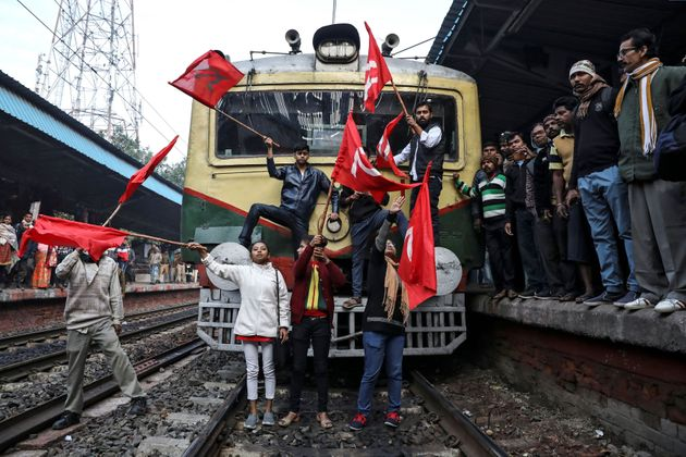 Supporters of the Communist Party of India-Marxist (CPI-M) block a passenger train during an anti-government...