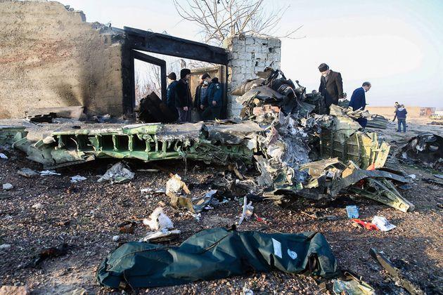 Pessoas próximas aos destroços da aeronave que caiu em Teerã e deixou 176