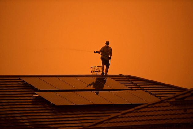 A resident uses a garden hose to wet down the house as high winds push smoke and ash from the Currowan...