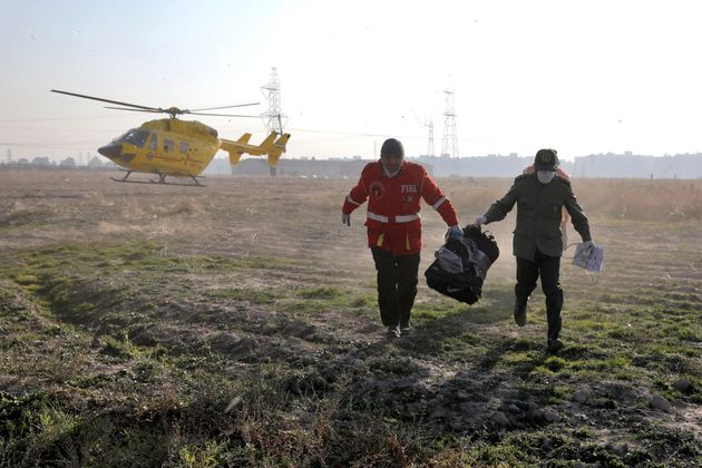 Rescue workers carry items retrieved from the scene where a Ukrainian plane crashed in Shahedshahr, southwest...