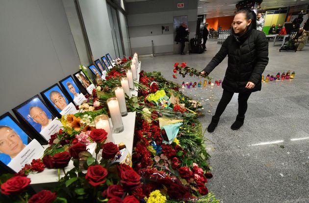 Una mujer coloca flores ante las fotos de los pasajeros, en el aeropuerto deBoryspil, en