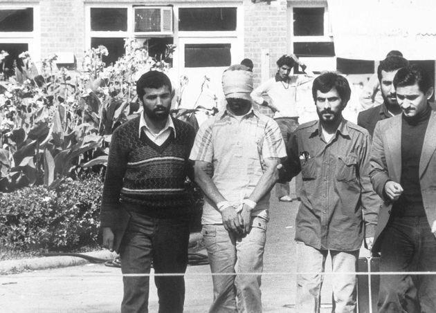 Un grupo de estudiantes iraníes muestra a la multitud a un rehén estadounidense retenido en la embajada...