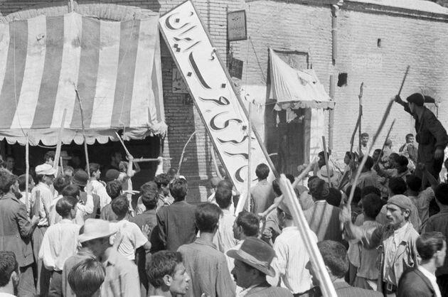 19 de agosto de 1953. Una multitud de manifestantes arranca el letrero del Partido Irán de una...