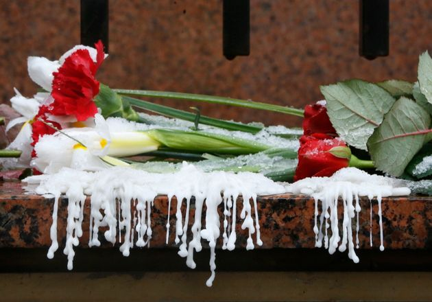 Wax from melted candles and flowers at the Canadian Embassy in Kyiv on Thursday, in memory of victims...