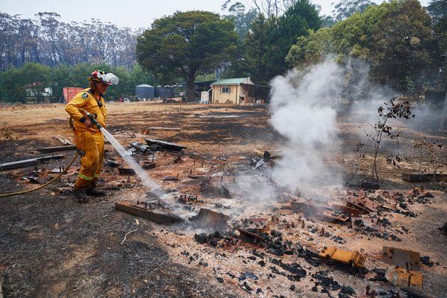 Un pompier arrose les restes fumants d'un