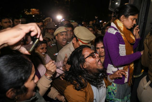 Police detain protesters during a march against the Jawaharlal Nehru University (JNU) violence, in New...