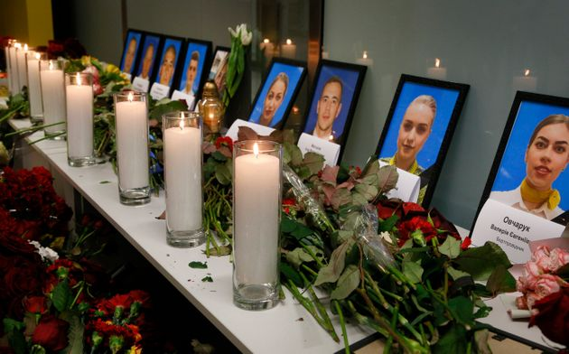 Flowers and candles are placed in front of portraits of the flight crew members of the Ukrainian 737-800