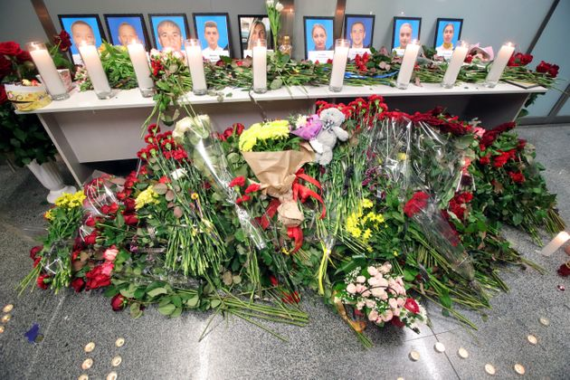 Flowers lay at the portraits of nine crew members who were killed at Boryspil International Airport in