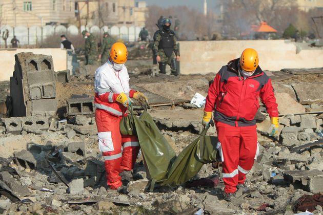 Equipes de resgate carregam corpo de vítima da queda do avião em Teerã, no