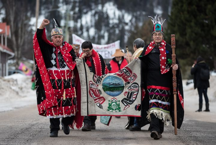 Heredity Chiefs Madeek (left) and Namoks carry a flag while leading a solidarity march to show support for the Wet'suwet'en Nation, in Smithers, B.C. on Jan. 16, 2019.