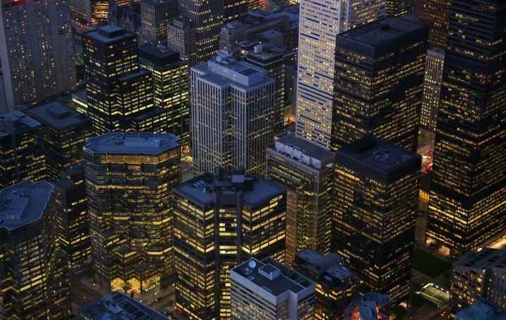 A night-time view of illuminated skyscrapers in the financial district of Toronto.
