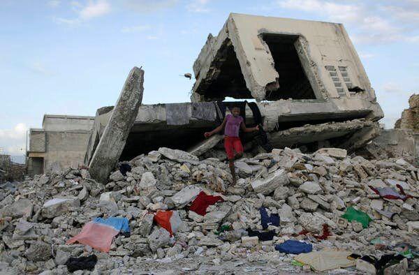 Quelques mois après le tremblement de terre, une fillette marche sur des débris alors qu'elle utilise la structure d'un bâtiment endommagé, à Port-au-Prince, pour sécher à l'air libre des vêtements.