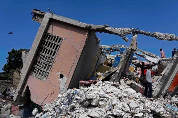 Des personnes se tiennent dans les décombres d'un bâtiment effondré à la suite du séisme, à Port-au-Prince.