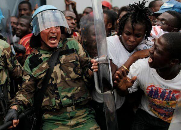 Un casque bleu péruvien tente de contrôler une foule pendant la distribution de nourriture pour les survivants du tremblement de terre dans un entrepôt à Port-au-Prince, le 19 janvier 2010. L'aide de l'ONU a été globalement inefficace.