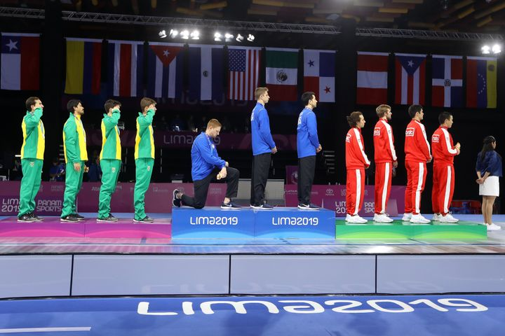Fencing gold medalist Race Imboden of the United States takes a knee during the national anthem at the Pan American Games on