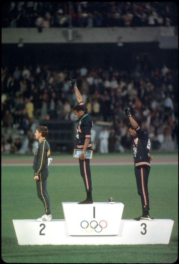 メキシコオリンピックで拳を突き上げて抗議をした、トミー・スミス選手(中央)とジョン・カーロス選手(右)