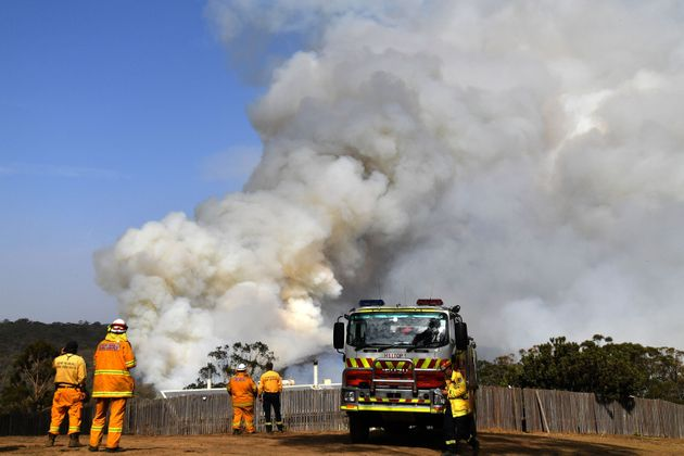 Firefighters work as smoke rises from a bushfire in Penrose, in Australia's New South Wales state on...