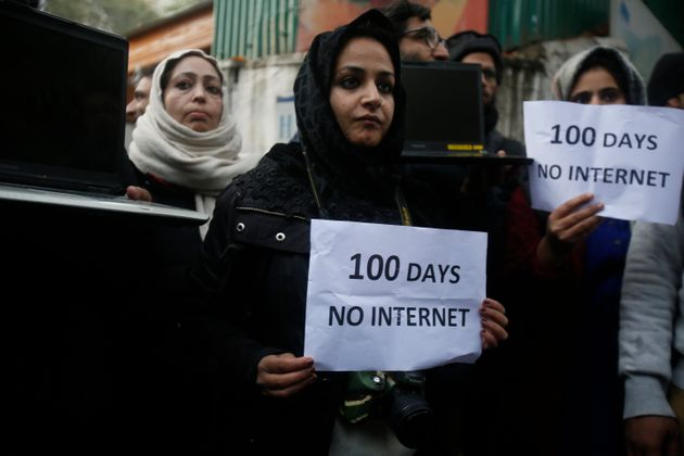 Kashmiri journalists hold placards and protest against 100 days of internet blockade in the region in...