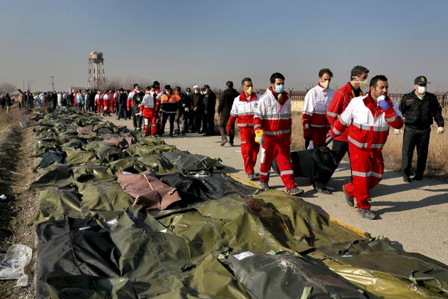 Rescue workers carry the body of a victim of a Ukrainian plane crash in Shahedshahr, southwest of the...