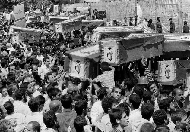 In this July 7, 1988 file photo, mourners carry coffins through the streets of Tehran, Iran, during a...