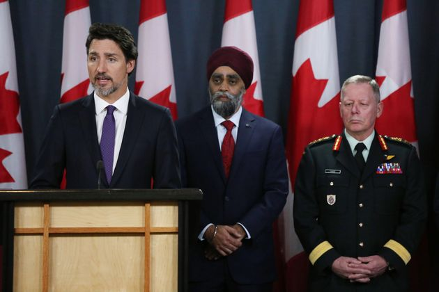 Prime Minister Justin Trudeau, left, speaks as Minister of National Defence Harjit Sajjan, centre, and...