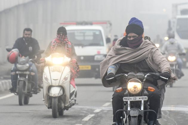 Commuters make their way on a road under heavy foggy conditions in Amritsar on January 9,