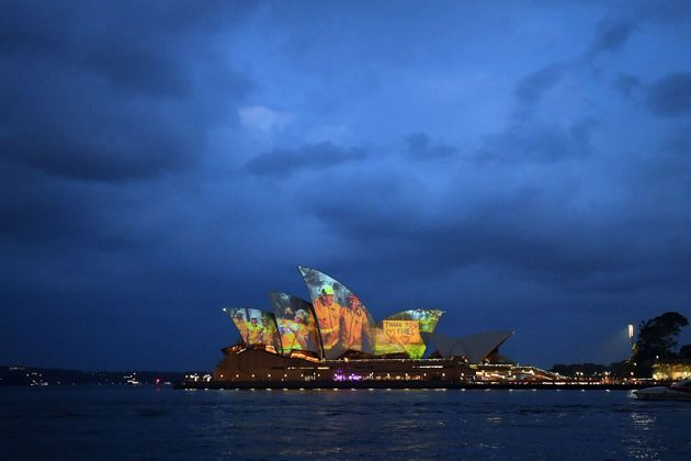 The sails of the Opera House are lit with a series of images to show support for the communities affected...