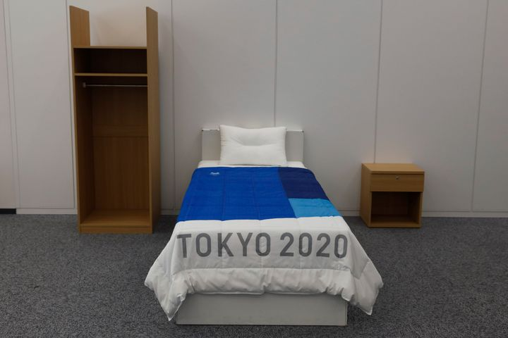 A set of bedroom furniture, including a cardboard bed, is photographed in a display room showing furniture for the Tokyo 2020