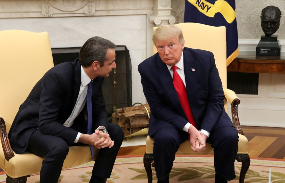 U.S. President Donald Trump listens to Greek Prime Minister Kyriakos Mitsotakis in the Oval Office of...