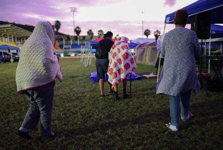 People get up after spending the night in a baseball stadium amid aftershocks and without electricity after the 6.4 magnitude