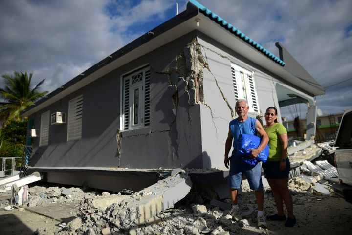 67 year-old William Mercuchi, center, and his daughter Joan pose for photos in front of their house that collapsed after the