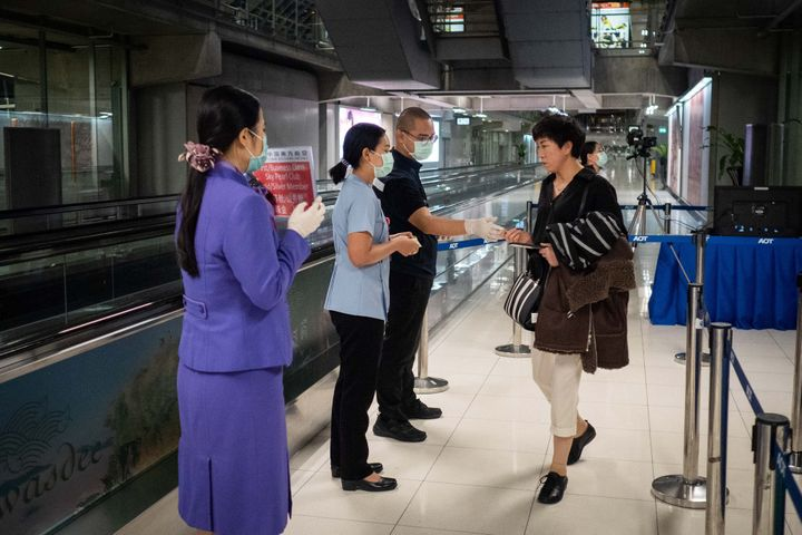 Public Health officials hand out disease monitoring information after performing thermal scans on passengers arriving from Wuhan, China at Suvarnabumi Airport.
