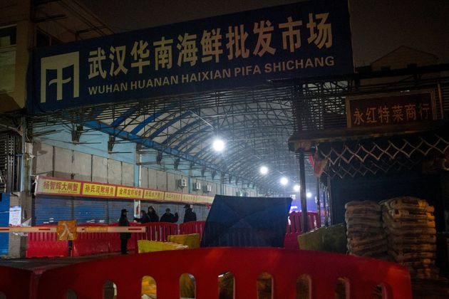 Security guards stand in front of the closed Huanan Seafood Wholesale Market in the city of Wuhan, in...