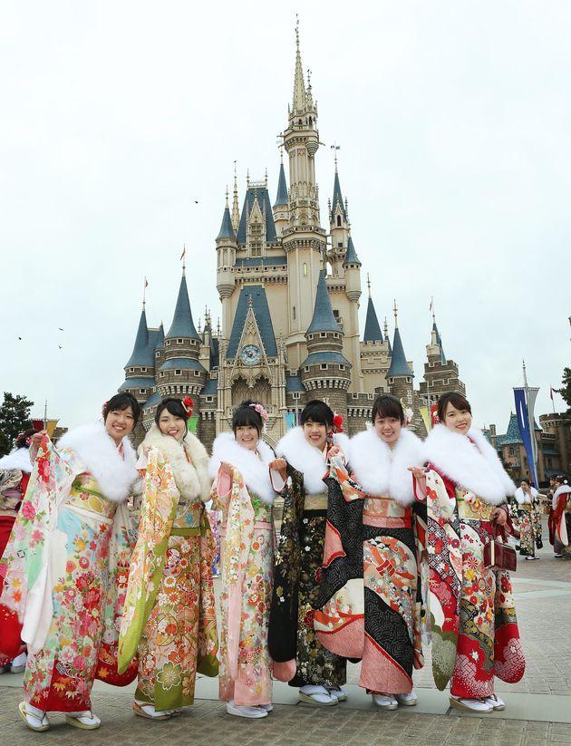 東京ディズニーランド(TDL)で成人式が行われ、シンデレラ城を背に晴れ着姿を披露する新成人=2018年1月8日、千葉県浦安市