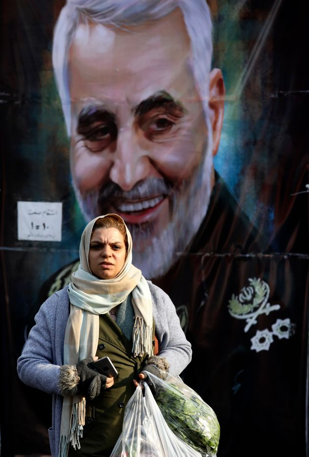 A women walks past a banner of Iranian Revolutionary Guard Gen. Qassem Soleimani, who was killed in Iraq...