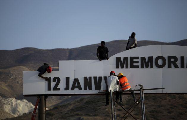 Funcionários trabalhando em 2016 na placa de entrada do memorial do terremoto de 2010, que fica...