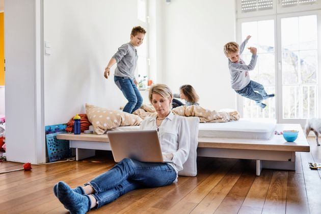 Mãe usa o computador em casa enquanto as crianças brincam. Segundo pesquisa, um dos motivos...