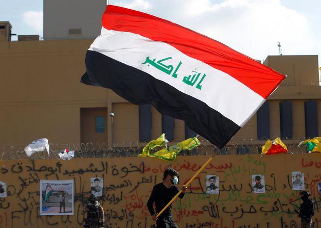 Manifestante agita bandeira iraquiana durante um protesto contra ataques aéreos em bases da forças...