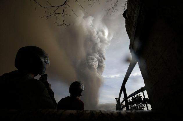 People watch as Taal Volcano erupts Sunday Jan. 12, 2020, in Tagaytay, Cavite province, outside Manila,...